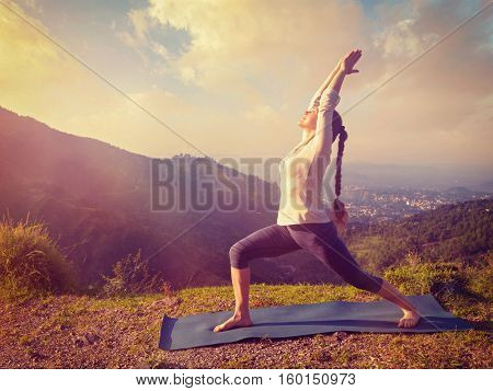 Yoga outdoors - sporty fit woman doing yoga asana Virabhadrasana 1 - Warrior pose posture outdoors in Himalayas mountains in the morning. Vintage retro effect filtered hipster style image.