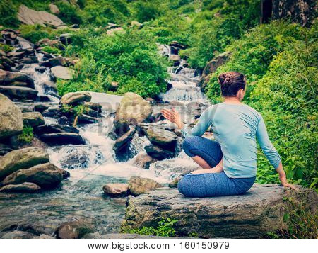 Yoga exercise outdoors -  woman doing Ashtanga Vinyasa Yoga asana Marichyasana D seated spinal twist pose at waterfall in mountains. Vintage retro effect filtered hipster style image.