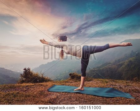 Yoga outdoors - sporty fit woman doing Ashtanga Vinyasa Yoga asana Virabhadrasana 3 Warrior pose posture in mountains. Vintage retro effect filtered hipster style image.