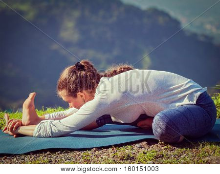 Yoga outdoors - woman doing Ashtanga Vinyasa yogaJanu Sirsasana A head to knee stretching asana position outdoors. Vintage retro effect filtered hipster style image.