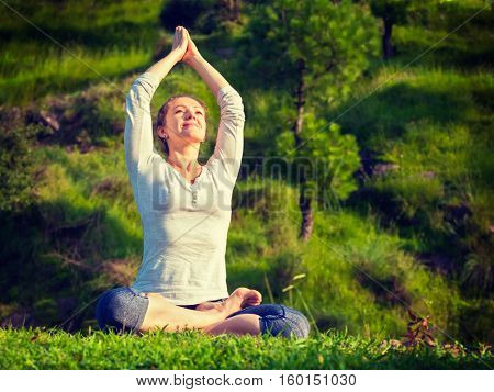 Meditation and relaxation yoga outdoors - young woman meditating and relaxing in Padmasana Lotus Pose) on green grass in forest. Vintage retro effect filtered hipster style image.