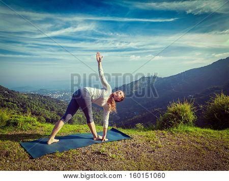 Woman doing Ashtanga Vinyasa yoga asana Parivrtta trikonasana - revolved triangle pose outdoors in mountains in the morning. Vintage retro effect filtered hipster style image.