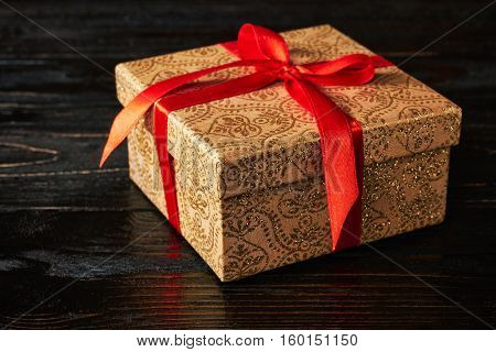 Gift birthday Christmas present concept - gift box with red ribbon on dark wooden background