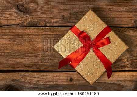 Gift present birthday Christmas concept - gift box with red ribbon on wooden background
