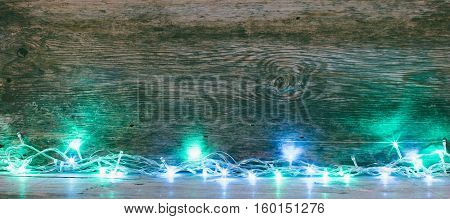 festive wooden background from old boards with lights. with space for text. the concept of a new year Christmas. tinted photo