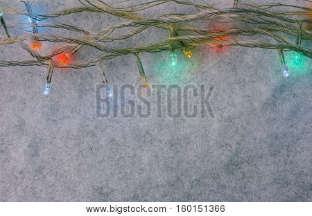 Christmas garland on the snow. Tinted photo with space for text