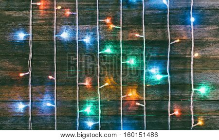 festive wooden background from old boards with a garland. with space for text. the concept of a new year Christmas. tinted photo