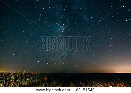 Starry night sky with the Milky Way over the field