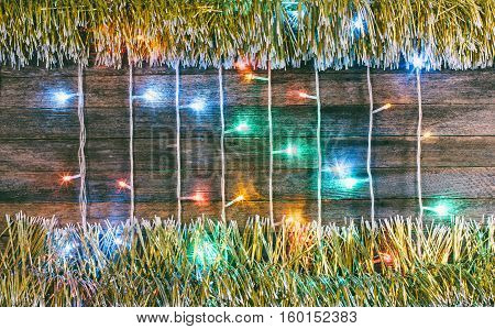 festive wooden background from old boards with colorful garland and gold tinsel. with space for text. the concept of a new year Christmas. tinted photo