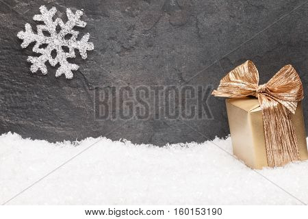 Christmas greeting card. Noel festive background. New year symbol. Gold gift box on snow. Festive background with copy space.