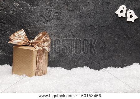 Christmas greeting card. Noel festive background. New year symbol. Gold gift box on snow.
