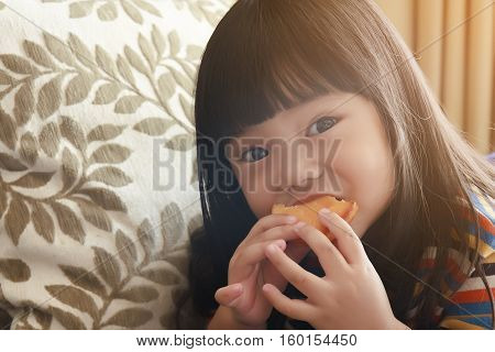 asian child or little girl enjoy eating a custard cake in the room with backrest pillow and sunlight