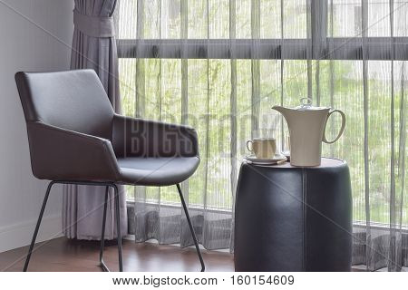 Ceramic Coffee Set On The Table With Black Leather Easy Chair In Living Room