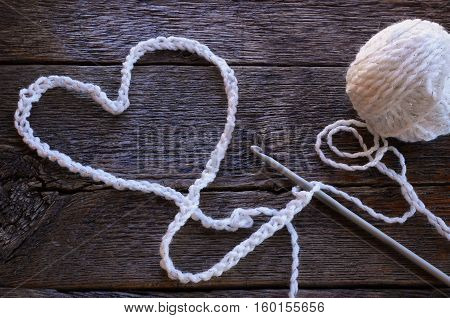 A top view image of a crochet hook and crochet yarn shape in a heart symbol on a wooden table top.