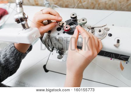 Seamstress replace bobbin in the sewing machine. Close-up of sewer hands preparing equipment for making clothes. Sewing process concept