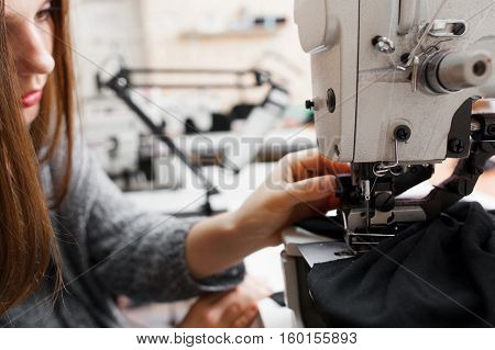 Female tailor fixing stuck fabric at equipment. Seamstress debugging problems with material while working. Garment industry, designer atelier, clothes making concept