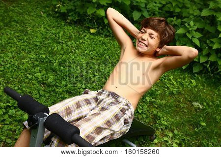 Young boy doing push-ups abdomen on a portable trainer outdoors in the countryside as he does his training exercises frontal view