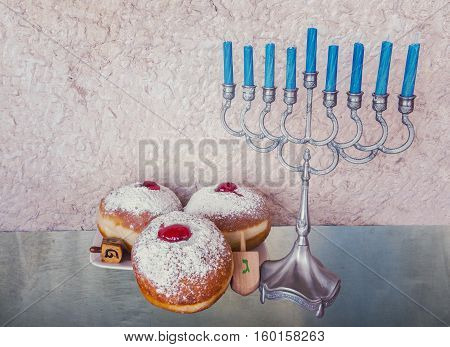 Jewish menorah with candles and sweet donuts are traditional symbols for Hanukkah holiday