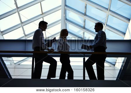 business people discussing something on top floor