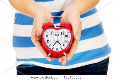 Teenage woman showing alarm clock