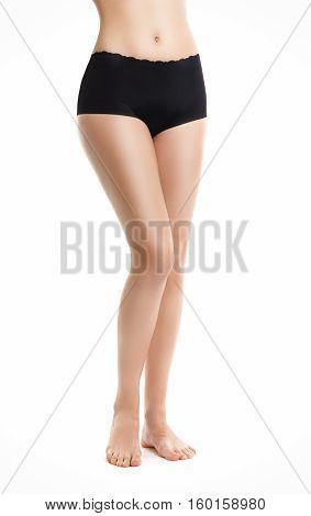 Slender Beautiful Female Feet. Woman In Black Shorts. Isolation On White