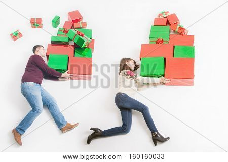 Black Friday 2016 at United States Funny mother and father shoppers holding many gift boxes for kids and running. Big gift box Cristmas shopping. Xmas, New Year holiday Merry Christmas