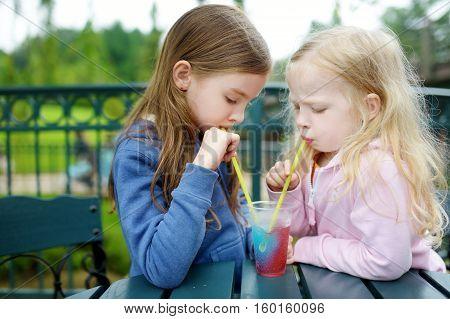Two Cute Little Sisters Drinking Frozen Slushie Drink