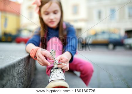 Cute Little Girl Learning To Tie Shoelaces Outdoors