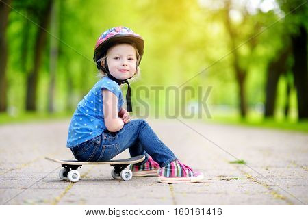 Cute Little Preteen Girl Wearing Helmet Sitting On A Skateboard