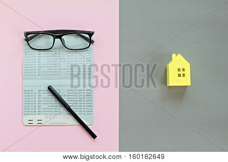 Business, mortgage or savings money concept : Savings account passbook, pen, glasses on pink background and yellow paper house on gray background