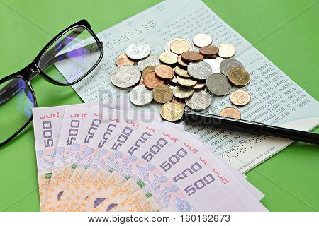 Business, finance or savings concept : Savings account passbook, Thai money baht, coins, glasses and pen on green background