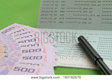 Business, finance or savings concept : Savings account passbook, Thai money baht and pen on green background
