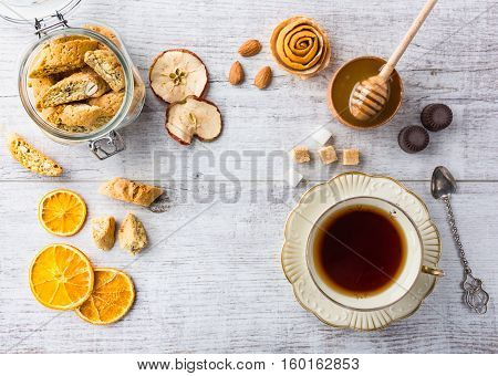 Tasty and healthy almond cookies, rich in vitamins, minerals in a glass jar, cup of tea, honey, almonds, chocolates, dried apples, dried lemons and sugar on white wooden table. Top view.