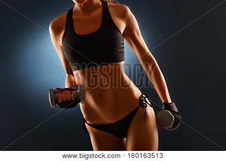 Midsection of woman lifting dumbells