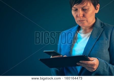 Smartphone and tablet data synchronization businesswoman syncing files and documents on wireless electronic devices at business office