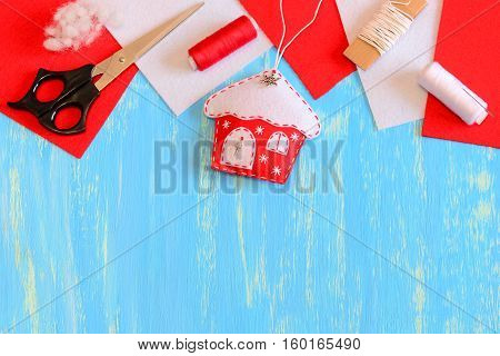 Felt Christmas tree house ornament, scissors, red and white thread, felt pieces, filler on a blue wooden background with copy space for text. Winter Christmas handmade crafts idea for kids. Top view