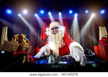DJ Santa Claus mixing up some Christmas event. Disco light around fun colorful atmosphere. Musical New Year.