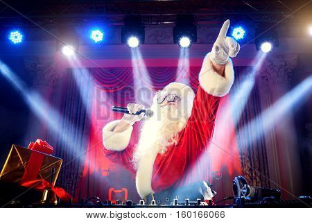 Dj Santa Claus mixing at the party at Christmas raised his hand up the other hand holding a microphone.