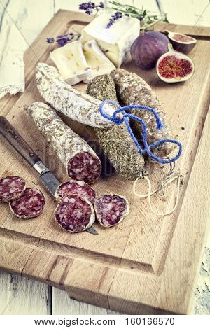 Salami with Cheese and Fig on Cutting Board