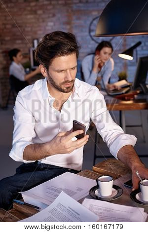 Businessman sitting at desk, using mobilephone, drinking coffee.
