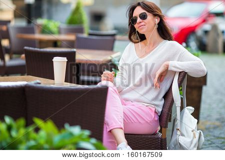 Young caucasian woman listening music in outdoor cafe