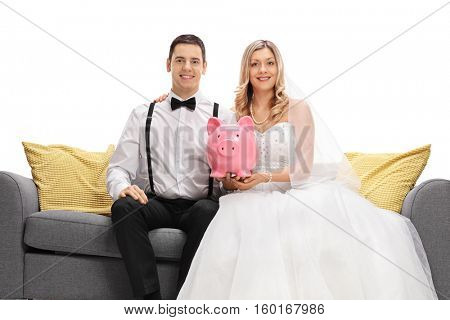 Newlywed couple sitting on a sofa and holding a piggybank isolated on white background
