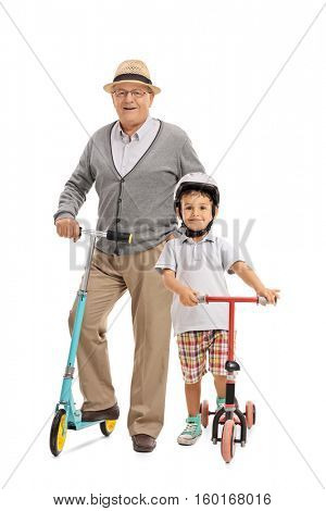 Full length portrait of an elderly man and a little boy with scooters isolated on white background