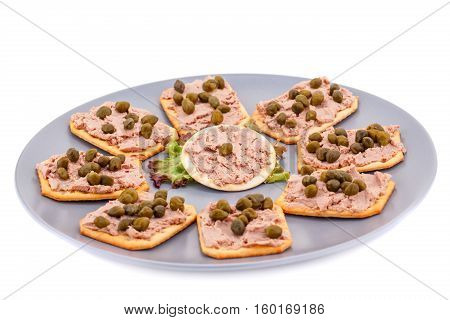Meat pate with capers on crackers and lettuce on plate isolated on white background.