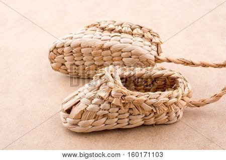 Pair Of Brown Color Straw Shoes On A Brown Background
