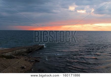 Lake at sunset and view of pier with bike tourists. Lake Baikal at sunset and a view of the pier with bike tourists.of tectonic origin in the southern part of Eastern Siberia, the deepest lake on the planet. Largest natural reservoir of fresh water.