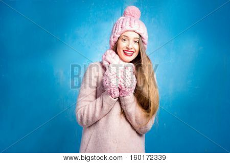 Winter portrait of a beautiful woman in knitted pink scurf, gloves and hat on the blue background
