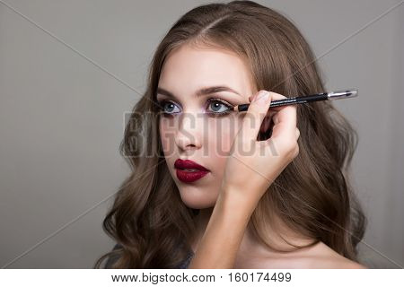 Make-up process, the face of a beautiful young woman and makeup artist's hand with a pencil for eyes. Cropped image