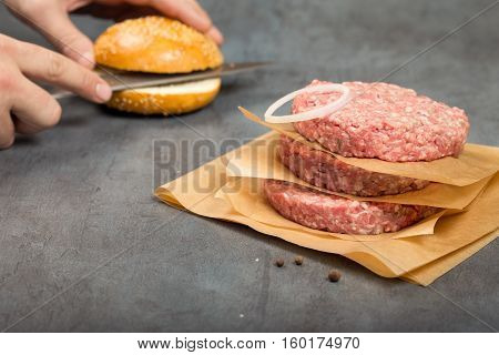 Raw ground beef meat cutlets with onion ring on a stone surface close up. In the background male hand prepared burger