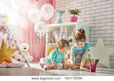 Happy children play. Little children girls draw with colored pencils indoors. Funny lovely children having fun in children room. Sisters playing together.